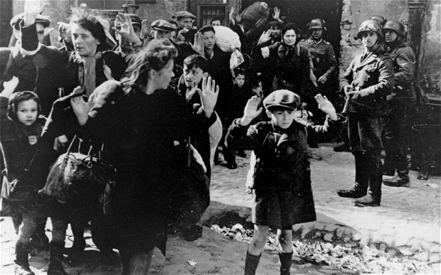 A group of Jews are escorted from the Warsaw Ghetto by German soldiers on April 19, 1943