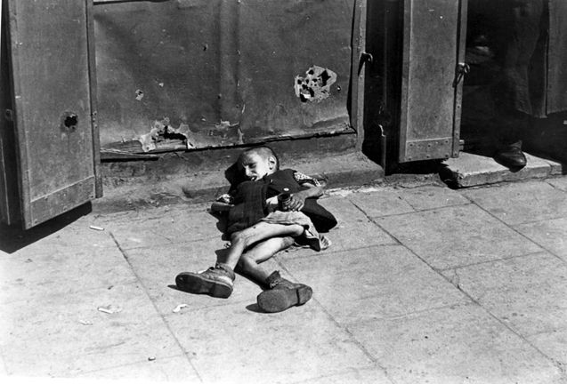 Warsaw ghetto, summer 1941, Poland, A boy lying in the street